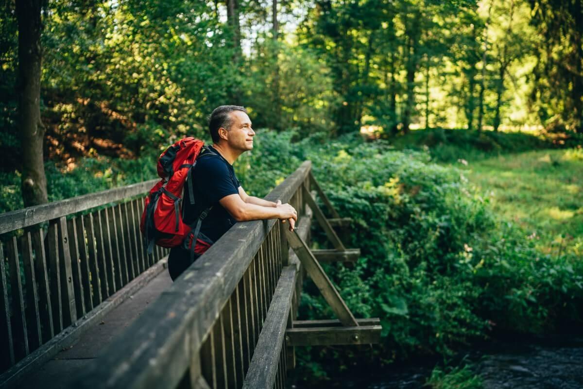 Mann mit Wanderrucksack steht auf der mitgenommenen Holzbrücke die über den Fluss führt, der den Polenztalweg kreuzt.