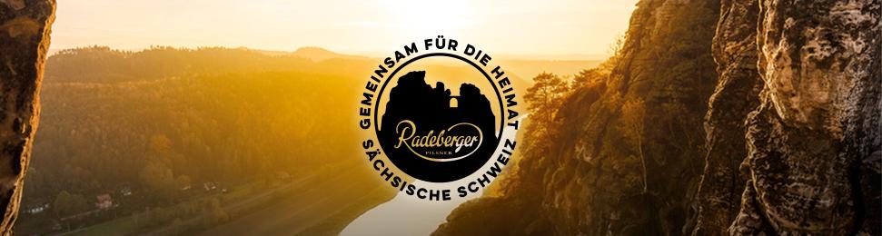 Schwarzes Aktionslogo mit einer Illustration der Bastei und der Beschriftung Gemeinsam für die Heimat sächsische Schweiz drum rum, Bild verlinkt auf die Aktionsseite.