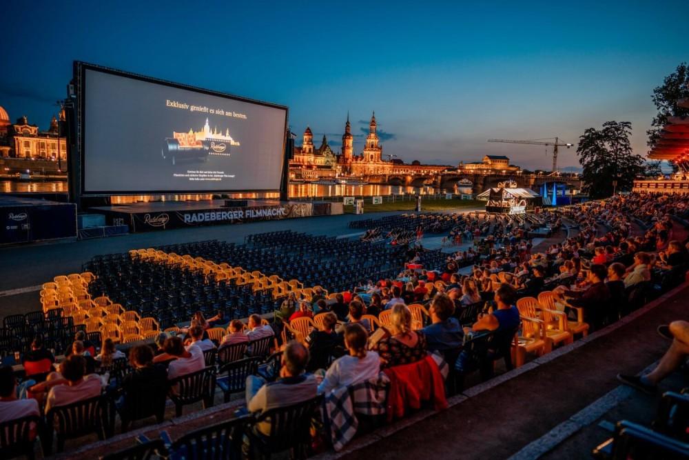 Blick auf viele Stühle und die Leinwand der Radeberger Filmnacht, auf der Leinwand ist ein Hinweis zum Radeberger Gewinnspiel zu sehen.